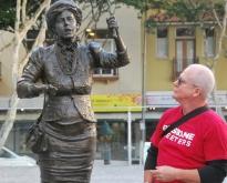 Brisbane Greeters guide Blair Allsopp with a statue of Brisbane suffragette Emma Miller