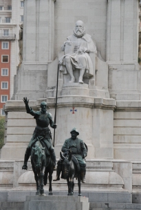 Monument to Cervantes in the Plaza de Espana, Madrid, with bronze statue of Don Quixote and Sancho Panza in front.