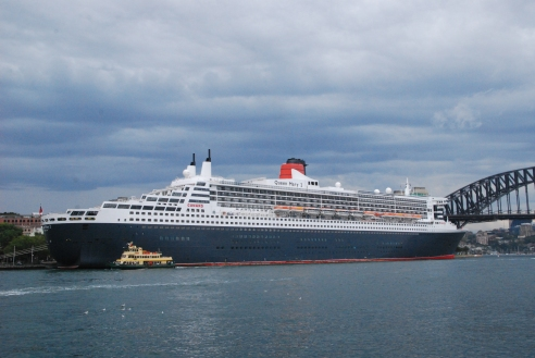 A Sydney ferry is dwarfed by the Queen Mary 2 at Circular Quay.